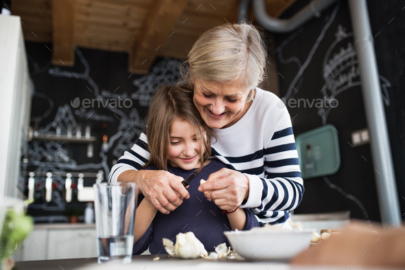 A small girl with grandmother cooking at home. - Stock Photo - Images
