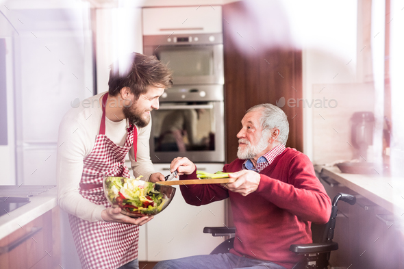 Son and senior father in wheelchair cooking in the kitchen. - Stock Photo - Images