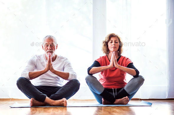 Senior couple meditating at home. - Stock Photo - Images