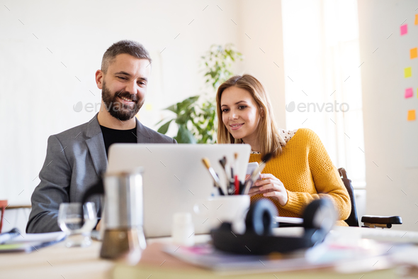 Two business people with wheelchair in the office. - Stock Photo - Images