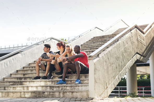 Young runners in the city sitting on the stairs. - Stock Photo - Images