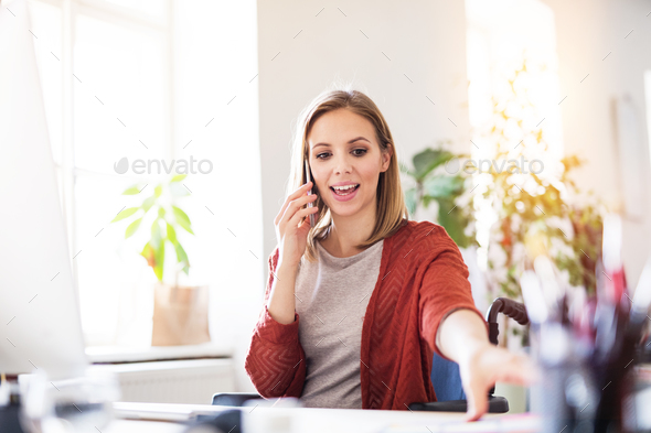 Businesswoman in wheelchair at the desk in her office. - Stock Photo - Images