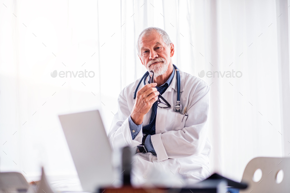 Portrait of a senior doctor in office. - Stock Photo - Images