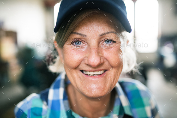 Portrait of a senior female mechanic in a garage. - Stock Photo - Images