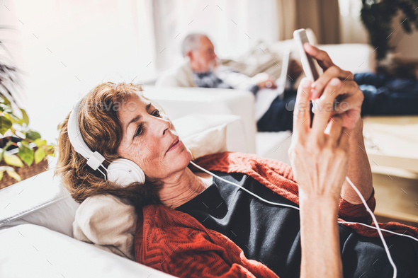 Senior couple with smartphone relaxing at home. - Stock Photo - Images
