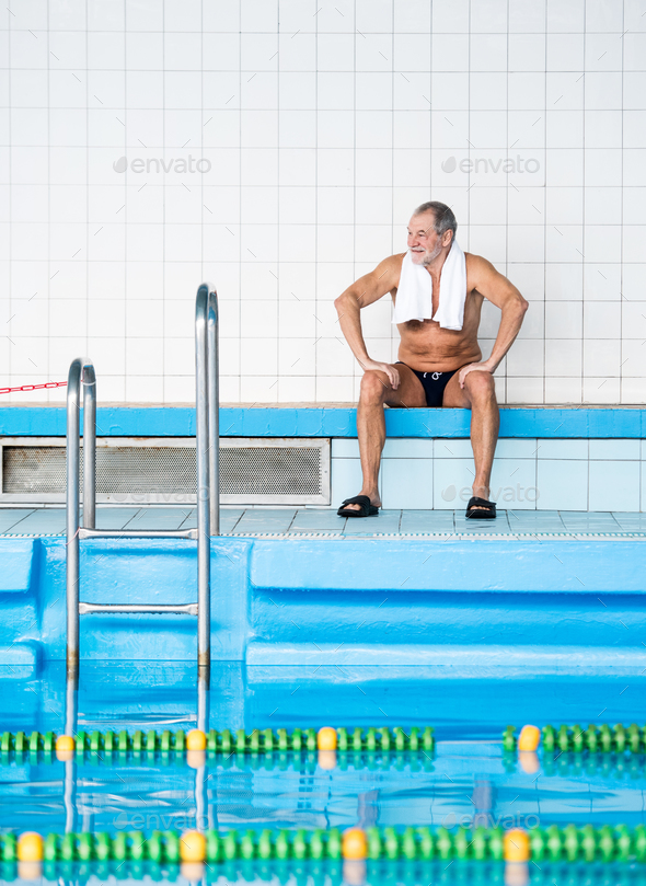 Senior man sitting by the indoor swimming pool. - Stock Photo - Images