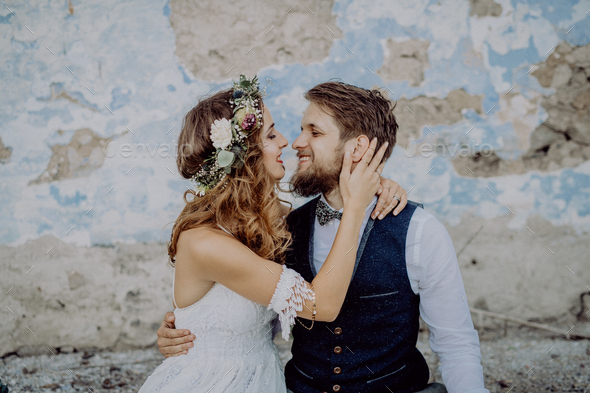 Beautiful bride and groom in front of old shabby house. - Stock Photo - Images