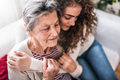 A teenage girl with grandmother at home, hugging. - PhotoDune Item for Sale