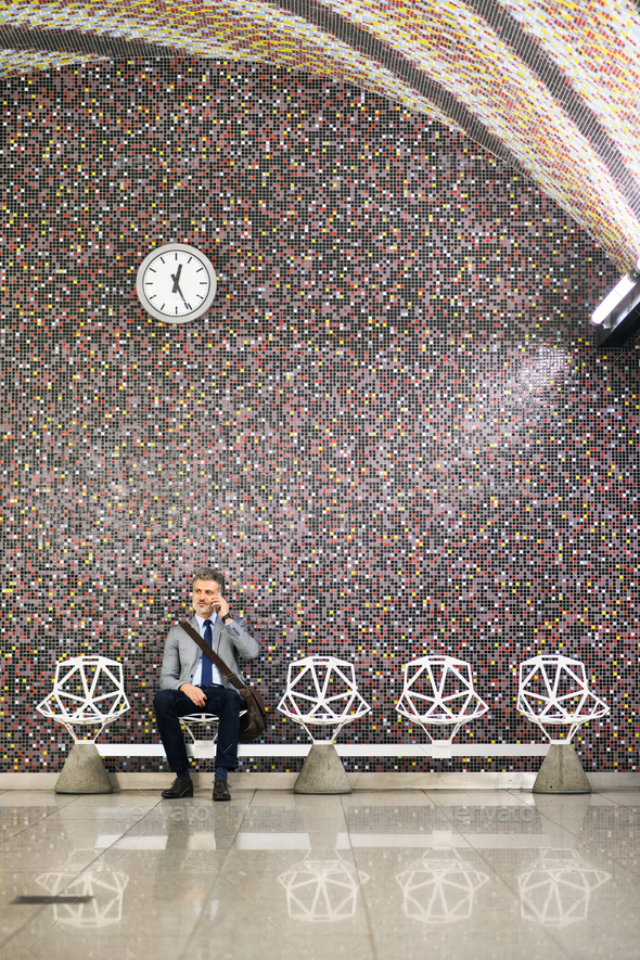 Mature businessman with smartphone in a metro station. - Stock Photo - Images
