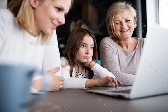 A small girl with mother and grandmother at home. - Stock Photo - Images