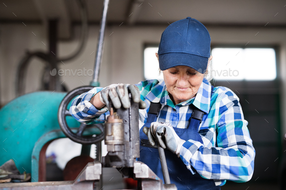 Senior female mechanic repairing a car in a garage. - Stock Photo - Images