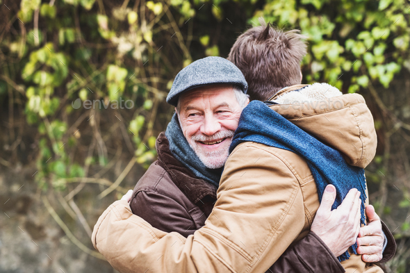Senior father and his young son on a walk, hugging. - Stock Photo - Images