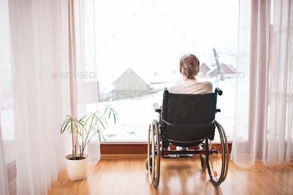 Senior woman in wheelchair at home. - Stock Photo - Images