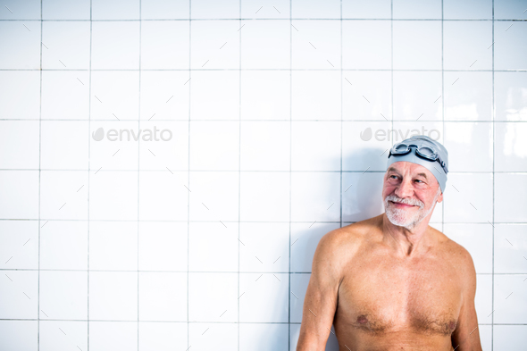 Portrait of a senior man in an indoor swimming pool. - Stock Photo - Images