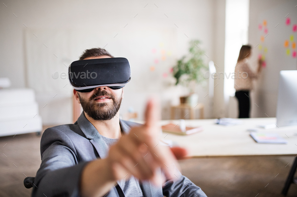 Two business people with wheelchair and VR goggles in the office. - Stock Photo - Images