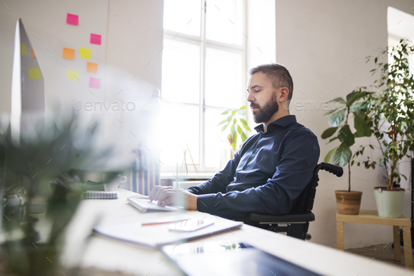 Businessman in wheelchair at the desk in his office. - Stock Photo - Images