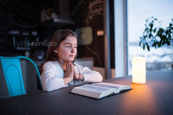 A small girl praying at home. - Stock Photo - Images