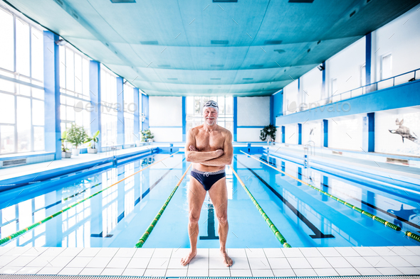 Senior man standing by the indoor swimming pool. - Stock Photo - Images