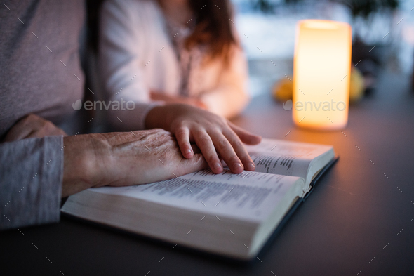 A small girl and grandmother reading bible at home. - Stock Photo - Images