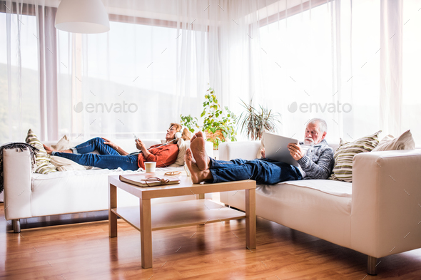 Senior couple with tablet and smartphone relaxing at home. - Stock Photo - Images