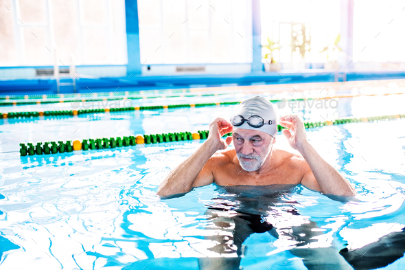 Senior man in an indoor swimming pool. - Stock Photo - Images