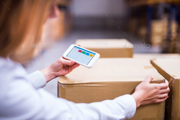 Woman warehouse worker or supervisor with smartphone. - Stock Photo - Images