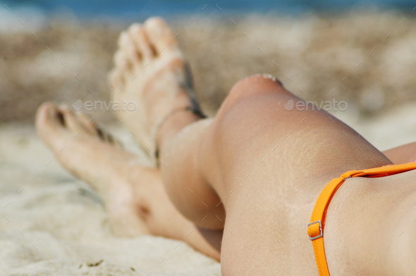 Female legs and feet on white sandy beach. Summer vacation concept - Stock Photo - Images