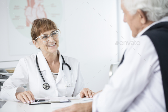 Doctor smiling at patient - Stock Photo - Images