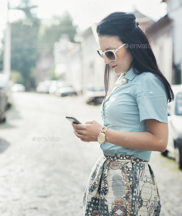 Fashionable woman texting on the street - Stock Photo - Images