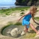 Little Adorable Girl Stands in a Volcanic Hole with Water at the Rock Beach Balangan in Bali - VideoHive Item for Sale