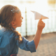 Girl playing with toy paper airplane - PhotoDune Item for Sale