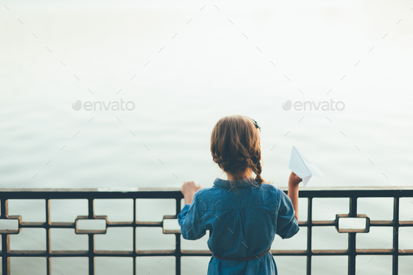 Girl with toy paper airplane looking to lake - Stock Photo - Images