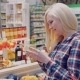 Girl Select Cheese in the Refrigerated Section at Store and Putting It Into the Basket - VideoHive Item for Sale