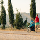 Mother with baby stroller running at sunset landscape - PhotoDune Item for Sale