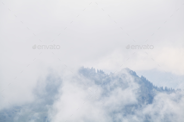 mountain peaks in dense fog - Stock Photo - Images