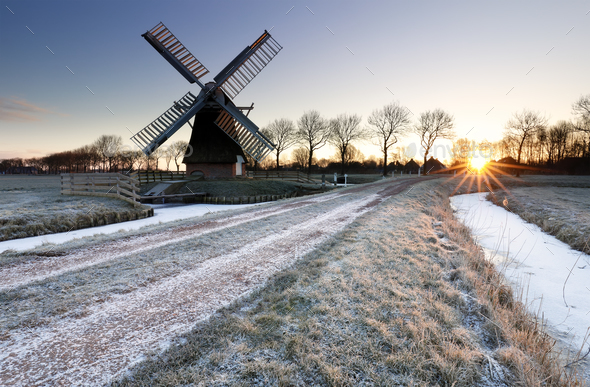 wintry sunrise over frozen countryside with windmill - Stock Photo - Images
