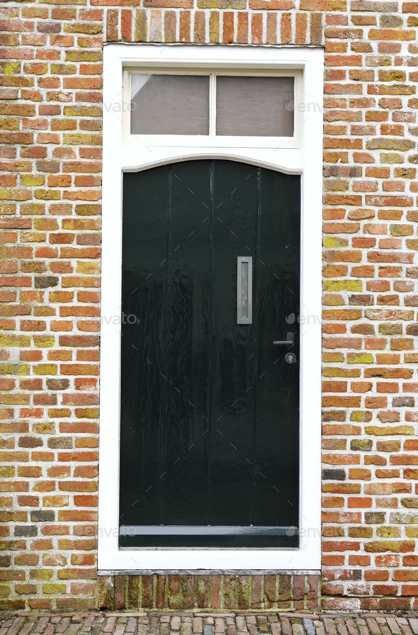dark greed door on brick wall - Stock Photo - Images