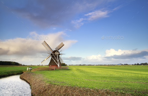 Dutch windmill on green meadow by river - Stock Photo - Images