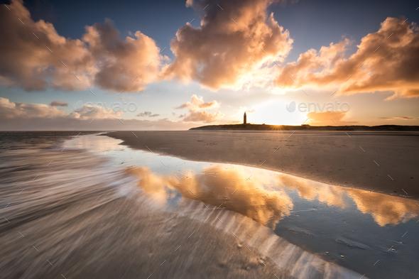 dramatic sunrise over North sea coast with lighthouse - Stock Photo - Images
