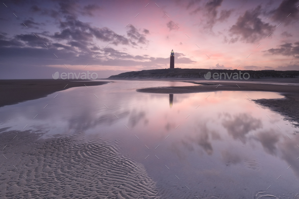 purple sunrise over North sea beach and lighthouse - Stock Photo - Images