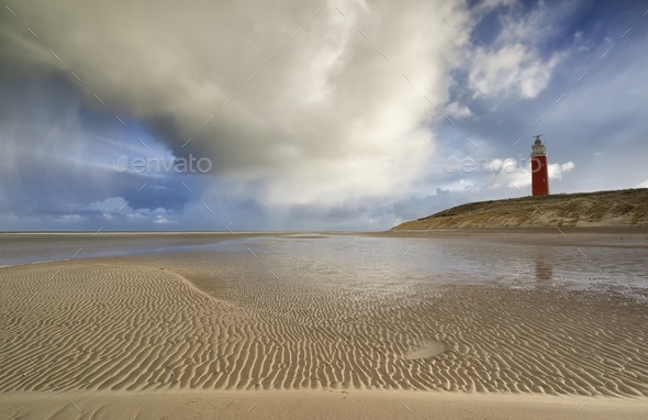 shower cloud over coast with red lighthouse - Stock Photo - Images