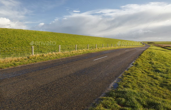 road between green grass hills  under blue sky - Stock Photo - Images