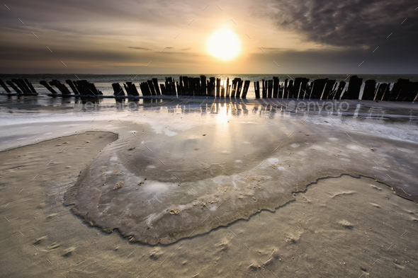 frozen waves by breakwater at sunset - Stock Photo - Images