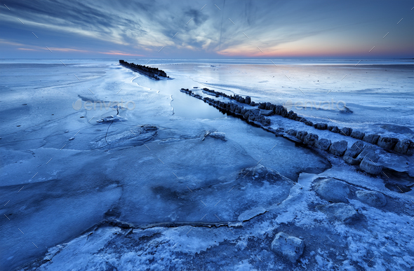 old wooden breakwater on frozen coast - Stock Photo - Images