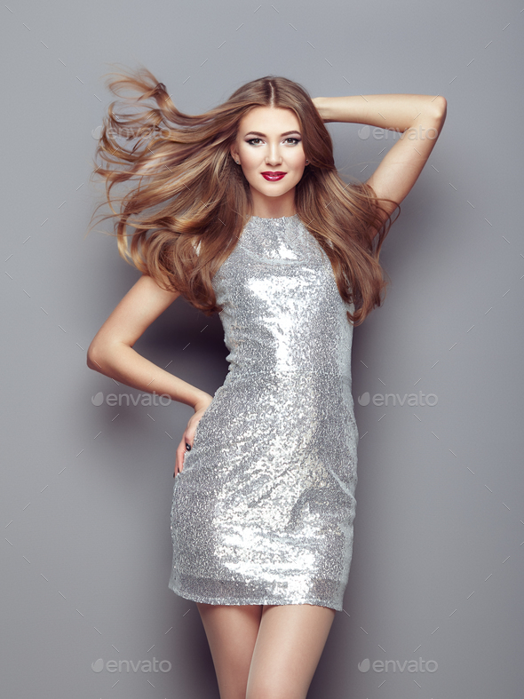 Fashion portrait young woman in elegant silver dress - Stock Photo - Images