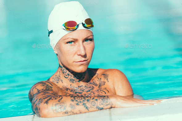 Portrait of female swimmer with tattoos posing by the pool - Stock Photo - Images