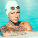 Portrait of female swimmer with tattoos posing by the pool - PhotoDune Item for Sale