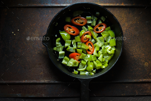 Green pepper and chili on a cast-iron frying pan copy space - Stock Photo - Images