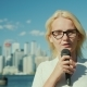 A Woman Journalist and TV Presenter Speaks Into a Microphone on a City Background. Toronto, Canada - VideoHive Item for Sale