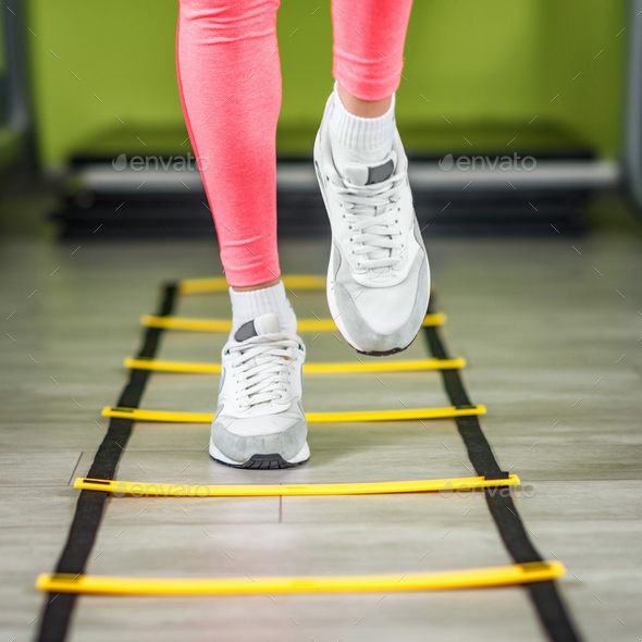 Woman exercising on ladders in the gym - Stock Photo - Images